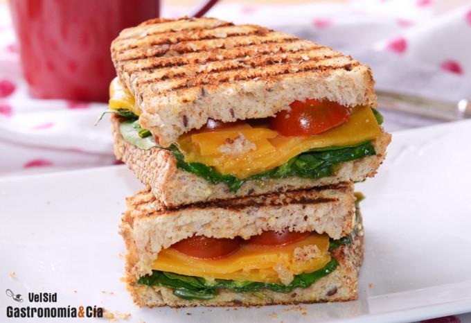 Bocadillo caliente de queso cheddar, espinacas y tomate