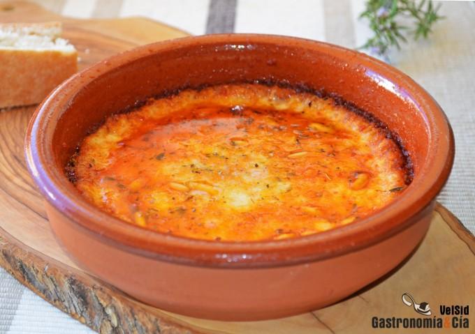 Provolone fundido con tomate, ajo asado y piñones